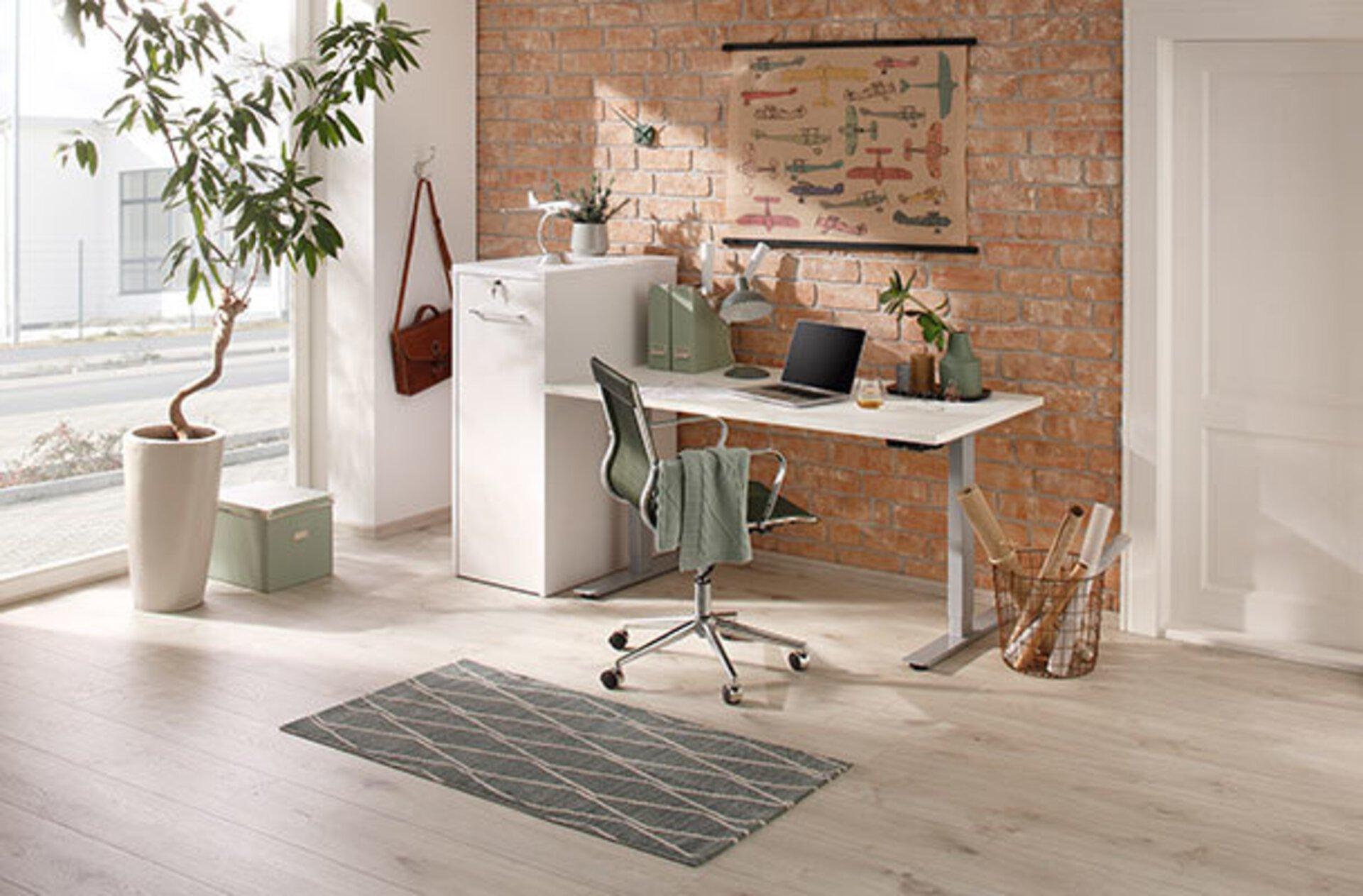 weißer höhenverstellbarer Schreibtisch an roter Backsteinwand. Davor ein schwarzer Drehstuhl mit Stoffbezug. Link steht ein Ficus Benjamini vor einer zimmerhohen Fensterfront.