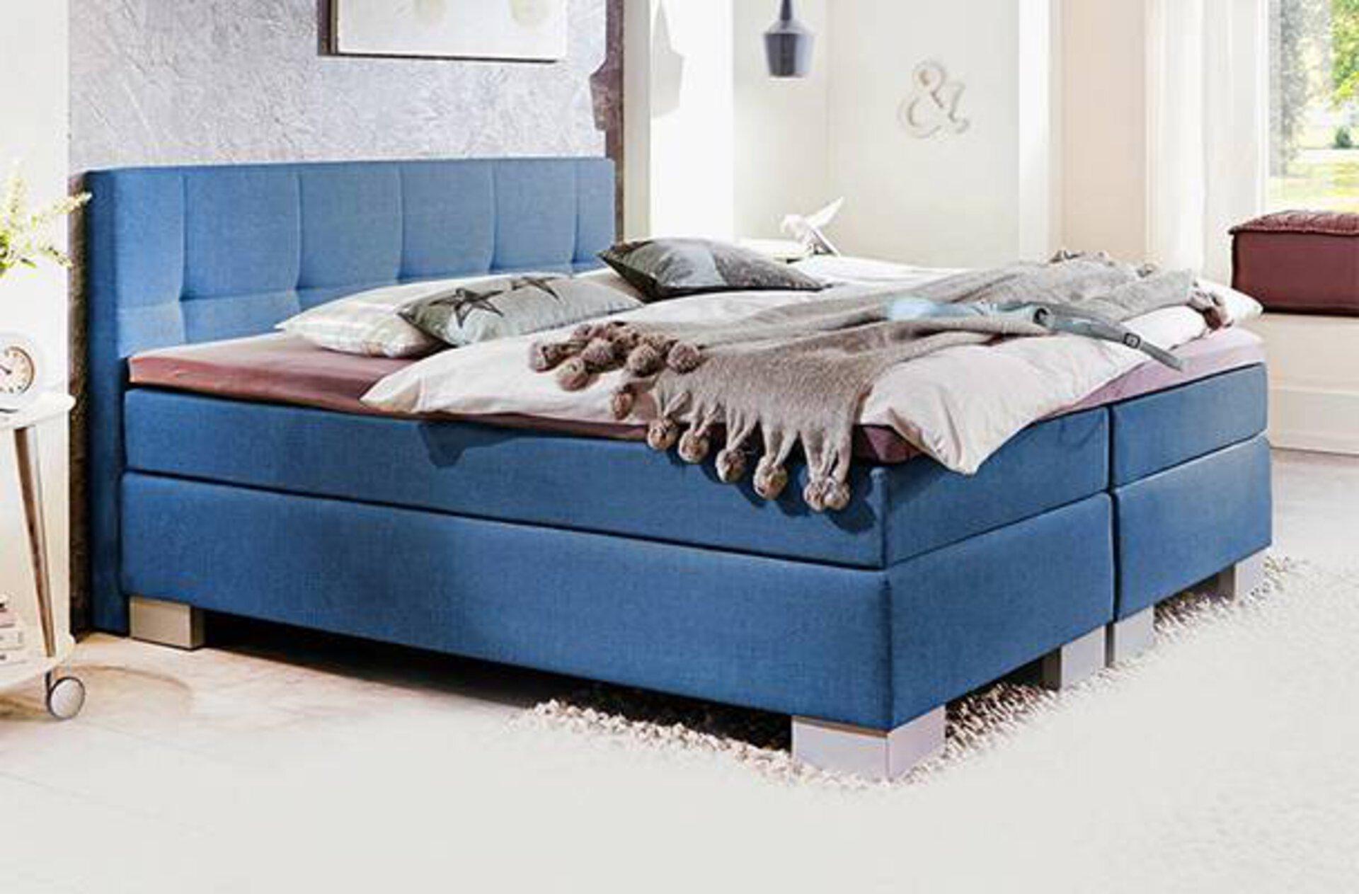 """Boxspringbett mit Doppelmatratze und blauem Bezugsstoff als erstes Bannerbild für den Inspirationsbereich """"Boxspringbett""""."""