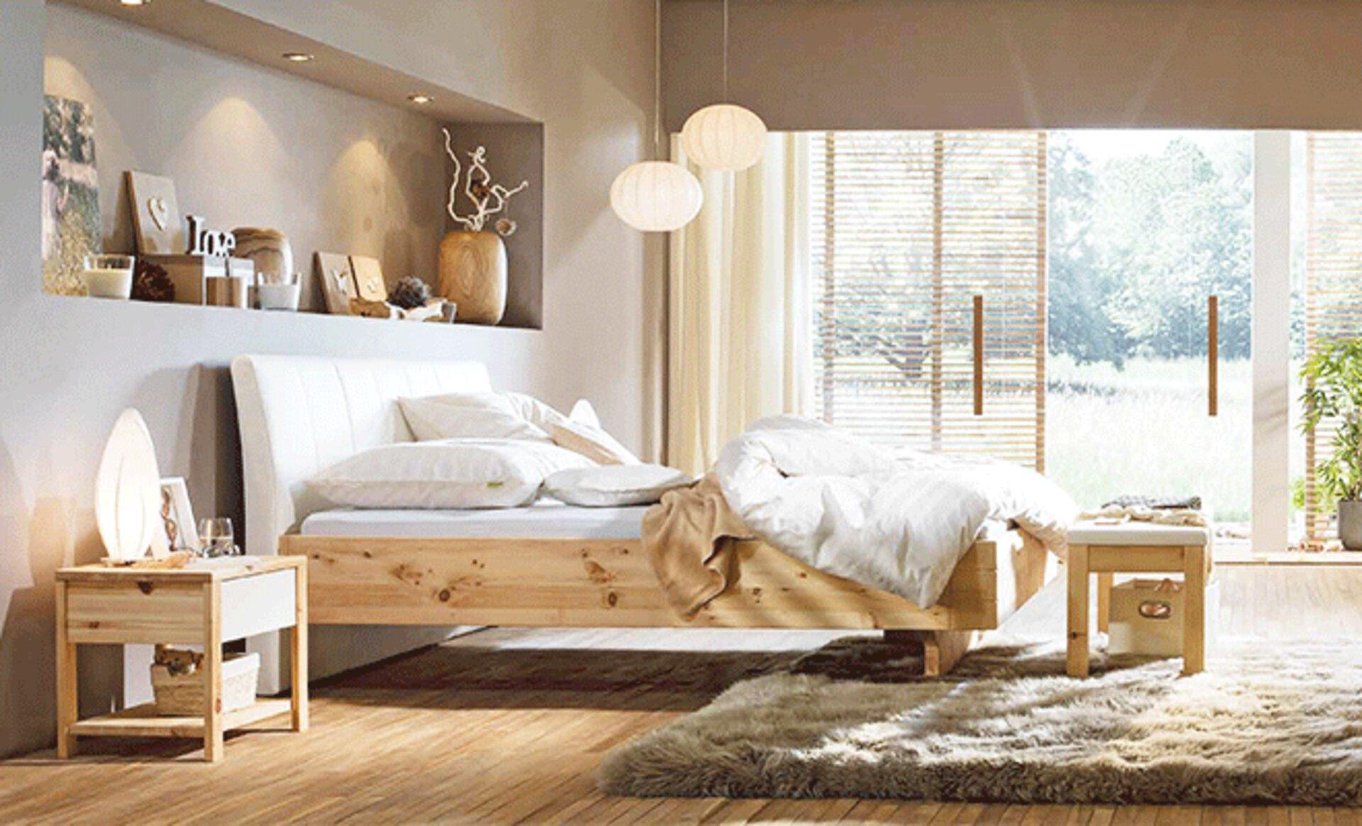 Schlafzimmerausschnitt im Landhausstil mit Bett und Schränken aus naturbelassenem Holz. Die Wand ist in warmem Beige gestrichen und auf dem Boden liegt ein flauschiger Hochflorteppich in dunklerem Beige.