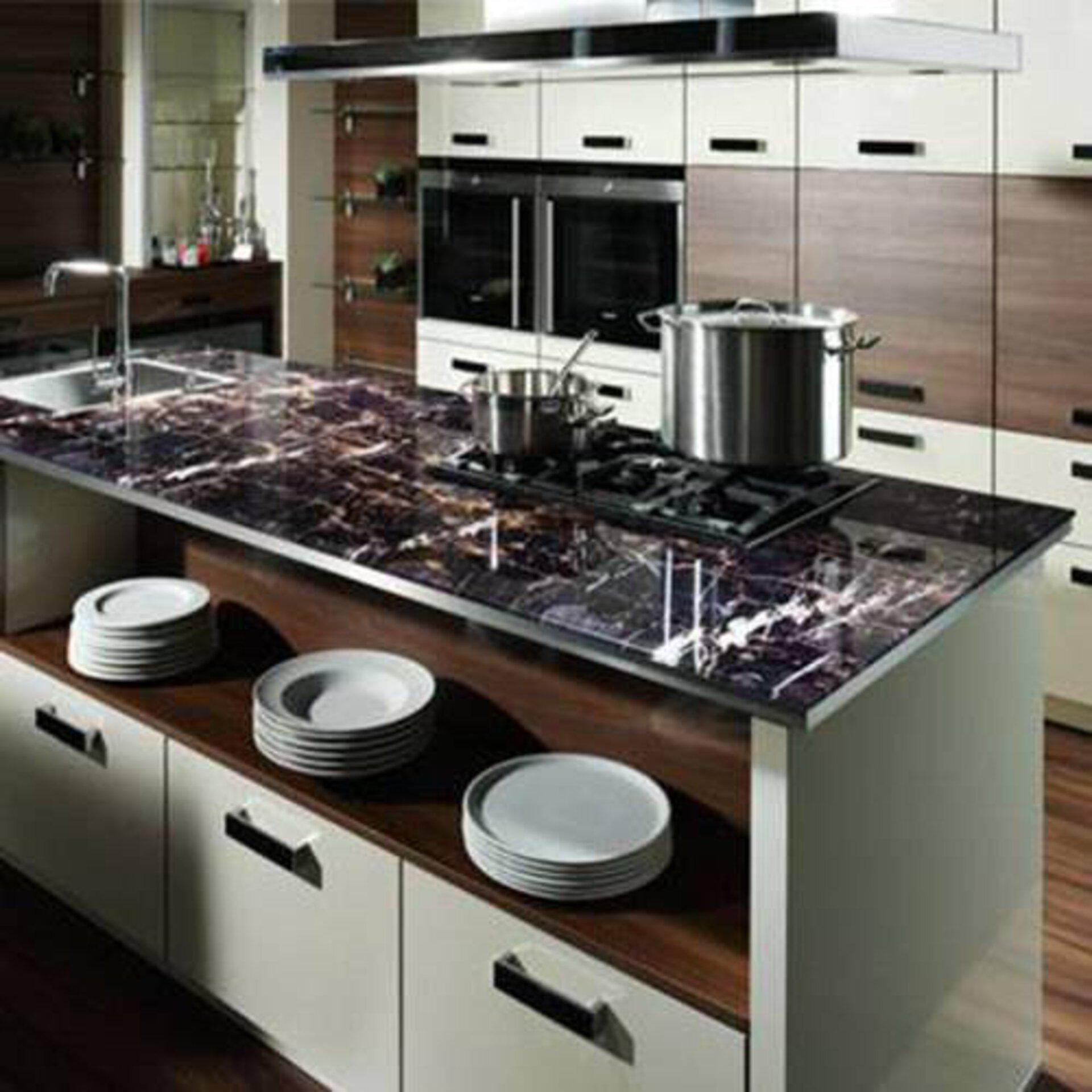 Millieubild für Arbeitsplatten aus Glas. Zu sehen ist eine moderne Kücheninsel mit marmorierter Arbeitsplatte in braun-rot Tonen mit weißen Einschlüssen.