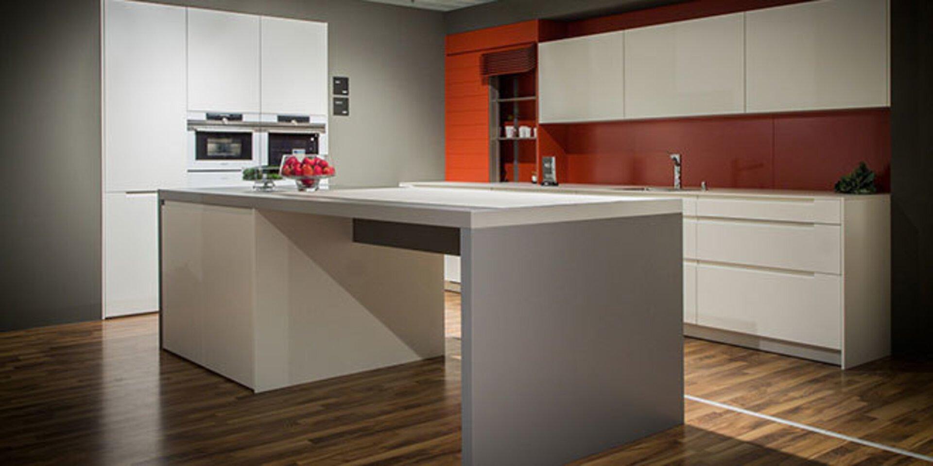 Eine moderne Premiumküche der Marke Leicht dient als weiteres Titelbild auf der Mrkenseite. Die dominierenden Farben sind weiß und rot