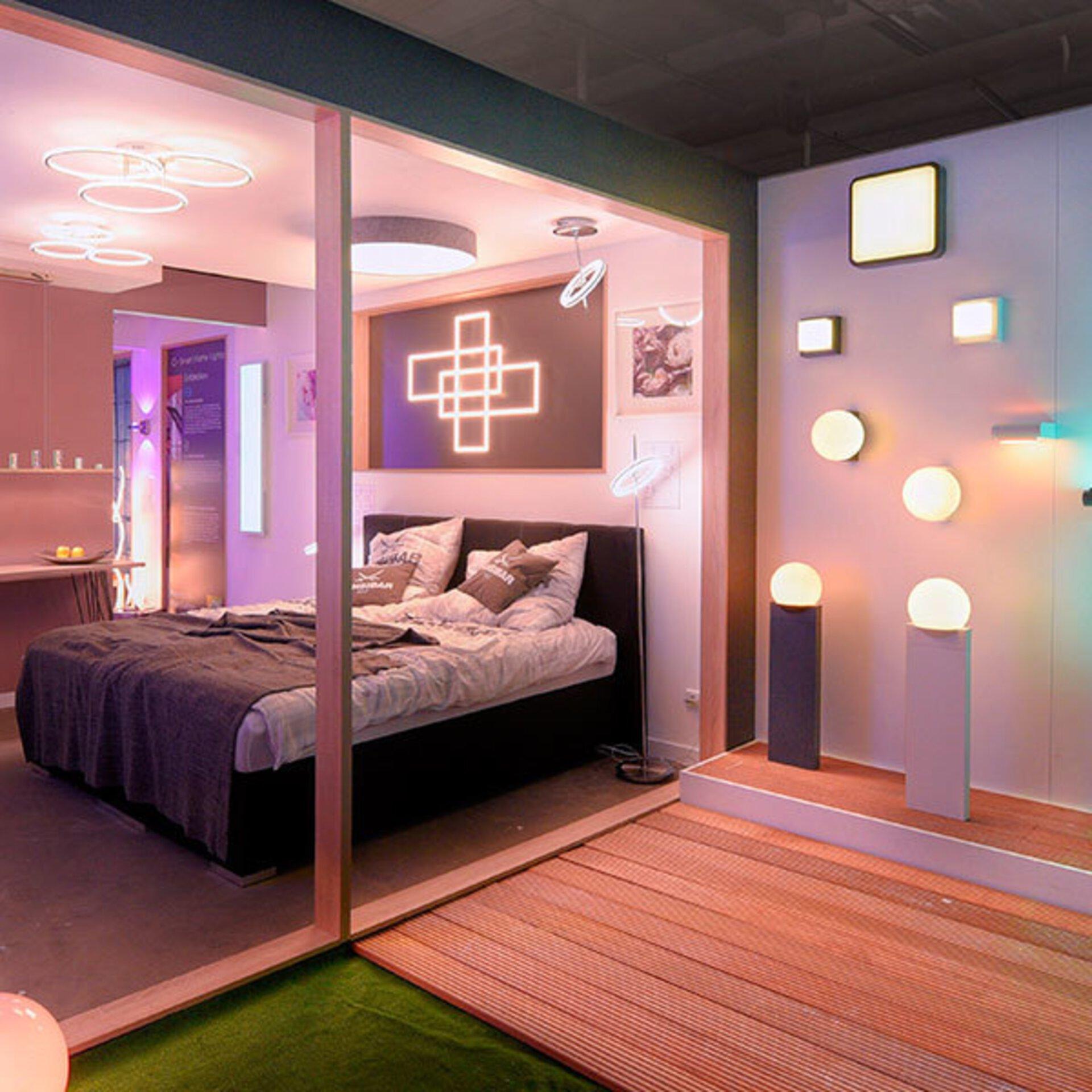 """Ein Ausstellungsraum der in verschiedene Lichtfarben geteilt ist, dient als Inspirationsbild für passende """"Smart Home Leuchten"""" innerhalb des Inspirationsbereichs."""