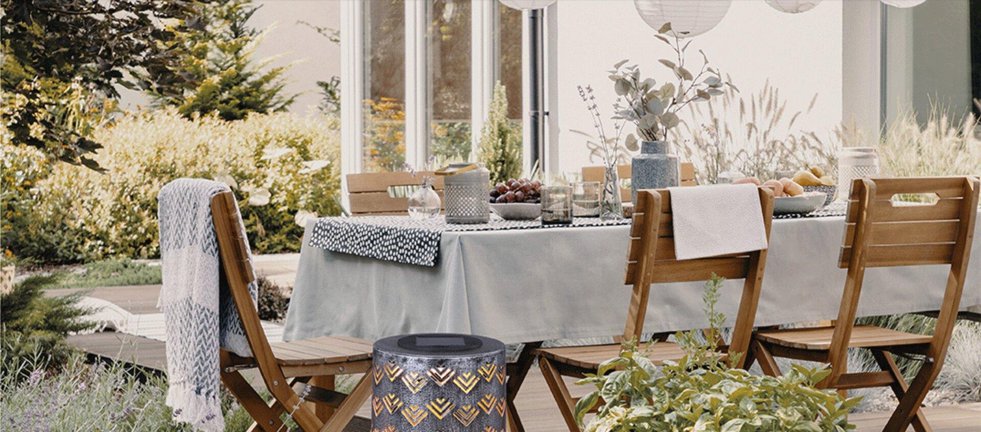 Ein romantisch gedeckter Tisch im Garten für einen lustigen Abend mit Freunden. Alles was Sie dazu benötigen finden Sie in der Outdoor und Gartenabteilung von Möbel Inhofer