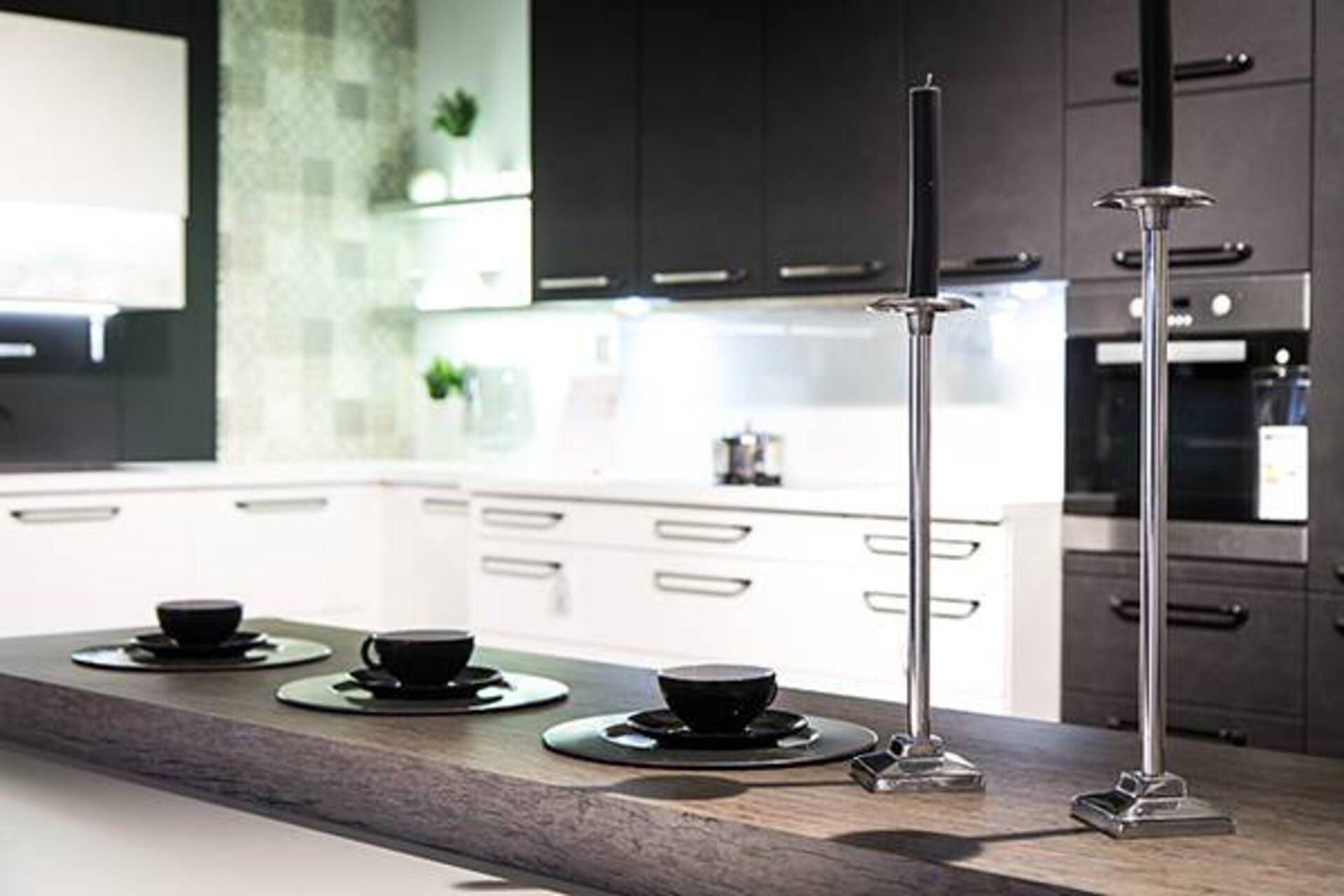 Kategoriebild zu Arbeitsplatten in der Küche. Zu sehen ist eine in die Küche integrierte Frühstückstheke mit dicker Arbeitsplatte aus grauem Naturstein.