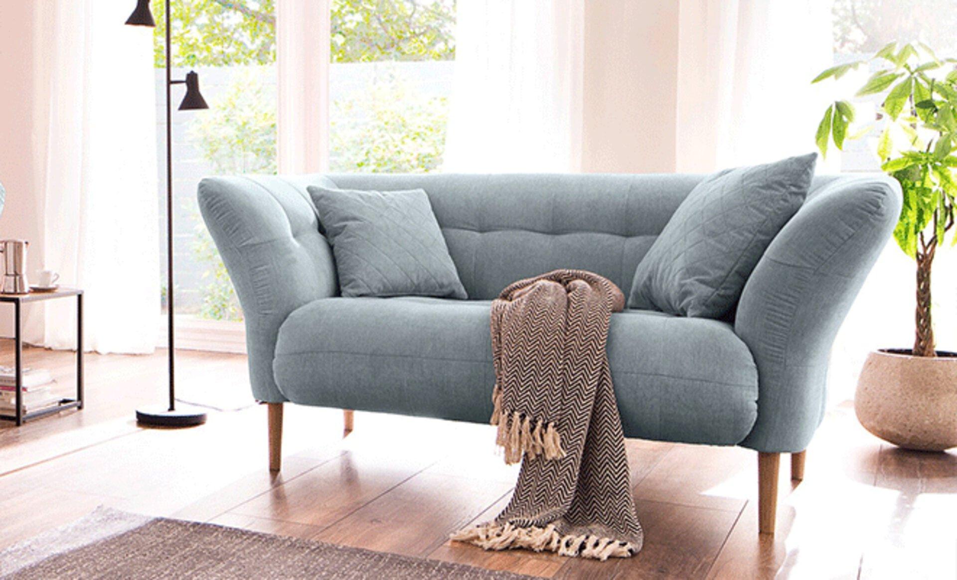 Zweisitzersofa mit hellblauem Stoffbezug, hoher Rücken- und Armlehne und naturbelassenen Holzfüßen. Typisches Einzelsofa im für das Einrichten im Landhausstil.