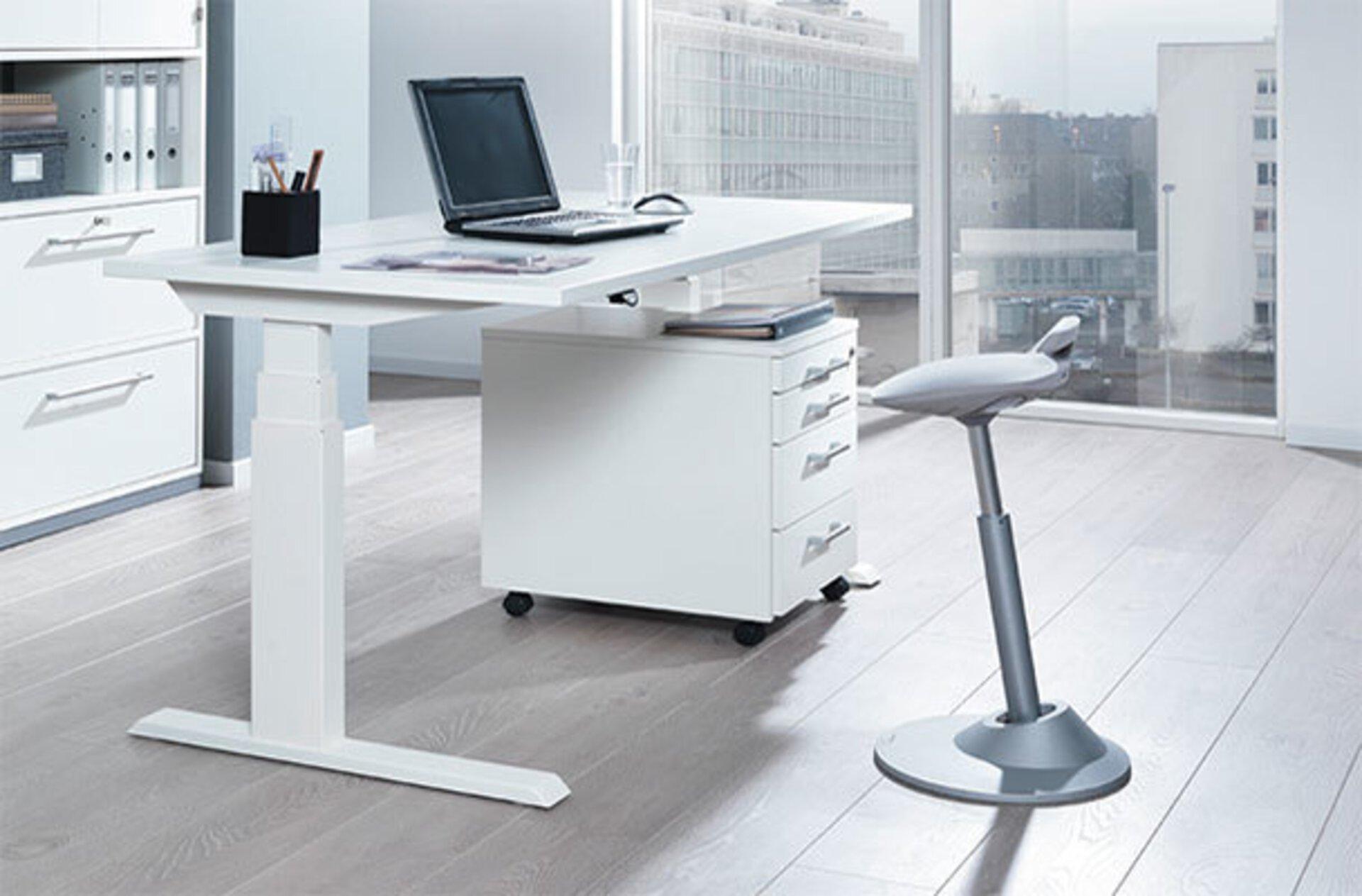 """Weißer höhenverstellbarer Schreibtisch und davor ein grauer , höhenverstellbarer Sitzhocker in ergonomischer Form. Das Bild dient als zweites Milieubild für den Bereich Inspiration """"Der richtige Bürostuhl""""."""