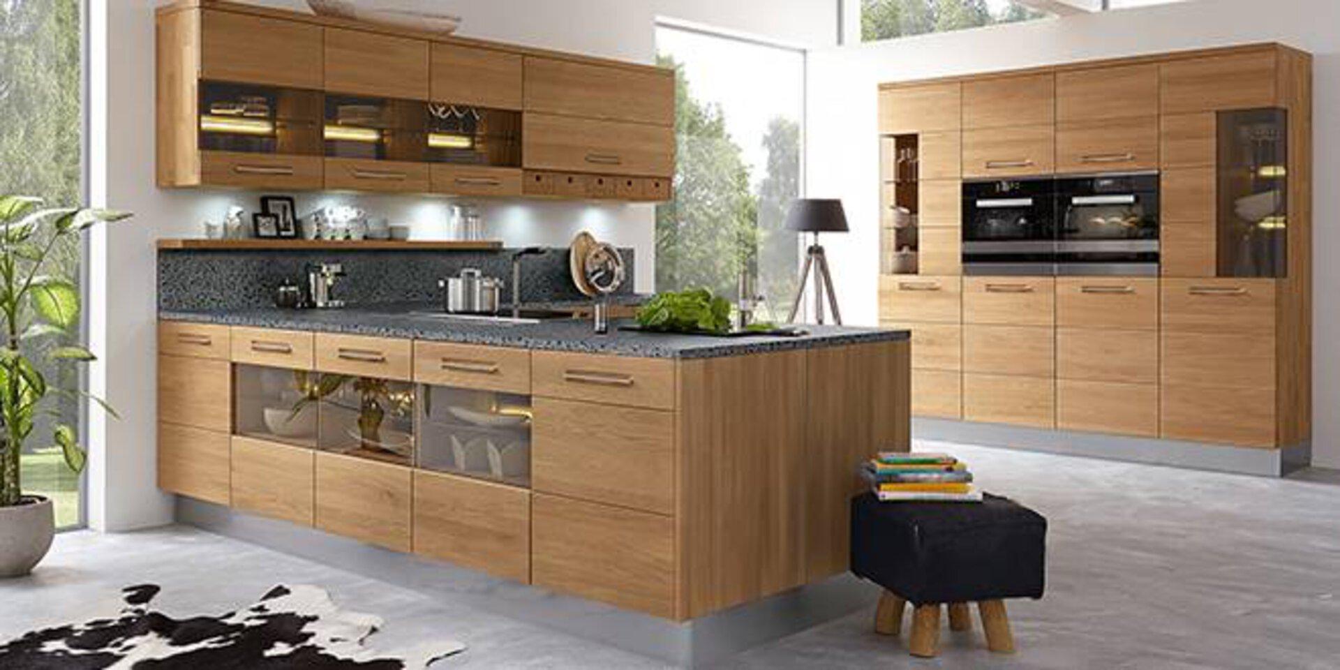 Moderne Küche aus Massivholz und Naturstein-Arbeitsplatte. Die Küche ist in L-Form gestaltet, wobei ein Teil als Kücheninsel den Raum zum Wohnbereich abtrennt. Die edle First-Calls-Küche ist von der Marke Decker.
