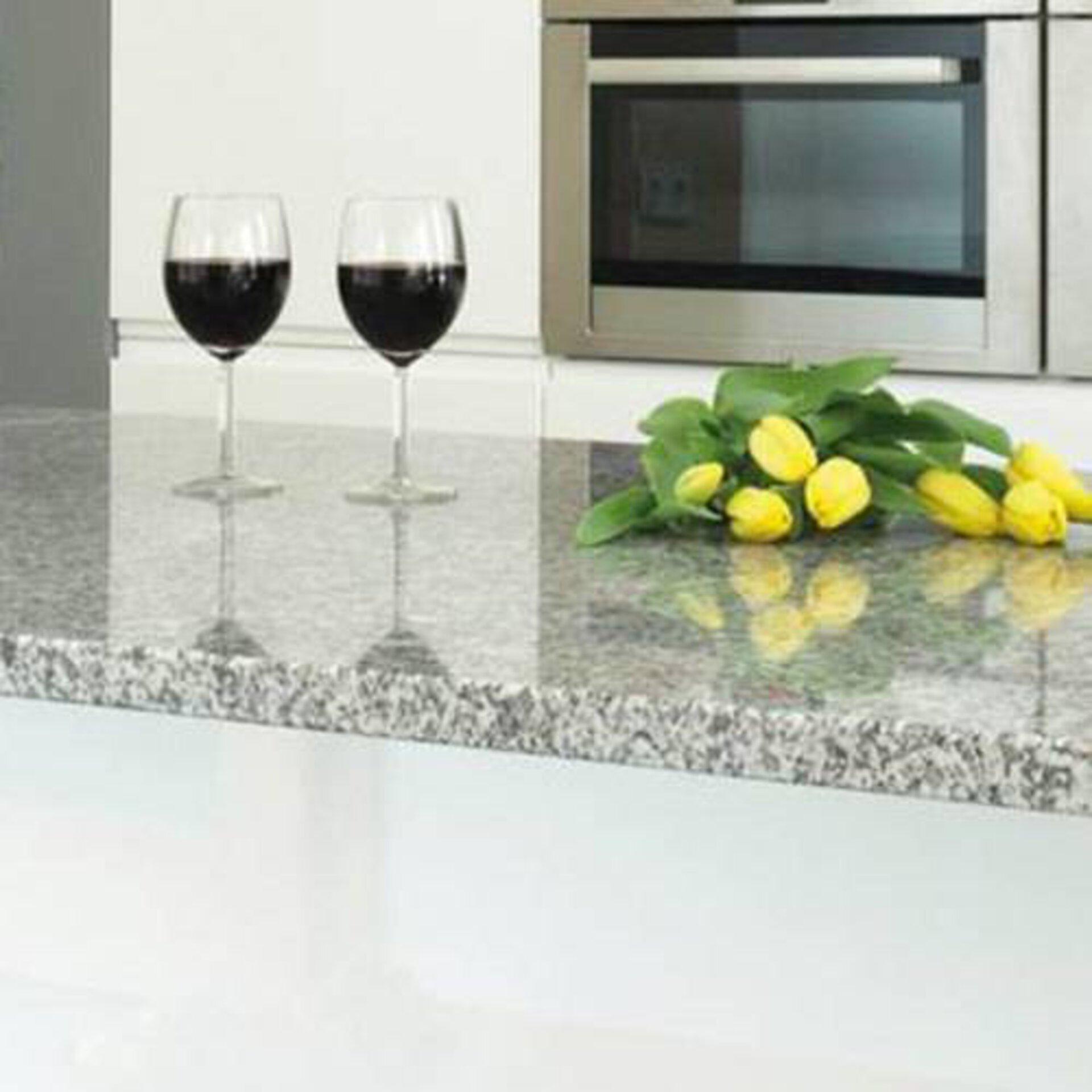 Milieubild zu Arbeitsplatten aus Naturstein. Zu sehen ist eine Küchenzeile mit grau gesprenkeltem Naturstein. Darauf stehen zwei Gläser Rotwein und ein Bund gelber Tulpen.