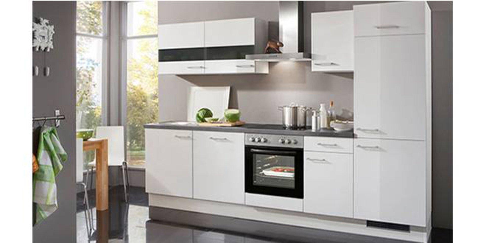Eine weiße Küchenzeile inklusive Hochschränken zeigt eine typische Kompaktküche.