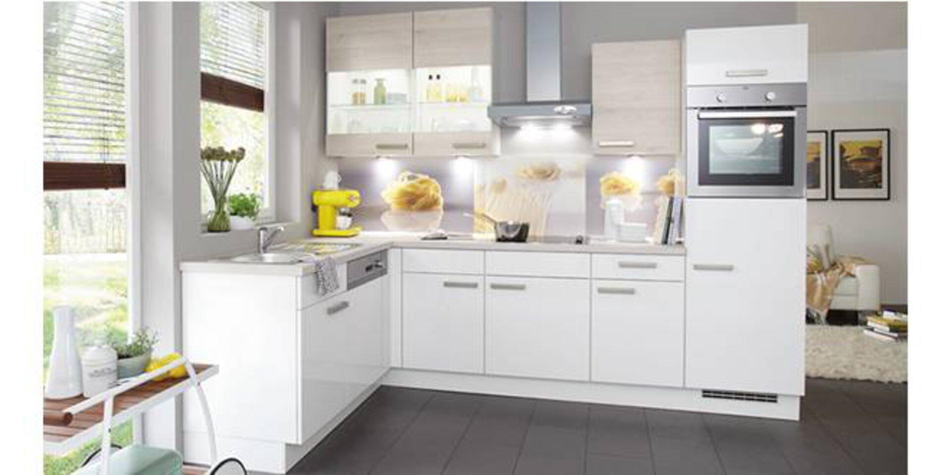 Weiße Küche in L-Form nützt perfekt die Ecke aus. Die abgebildete helle Küche mit Einbaugeräten und Hängeschränken zeigt eine mögliche Planungsküche.