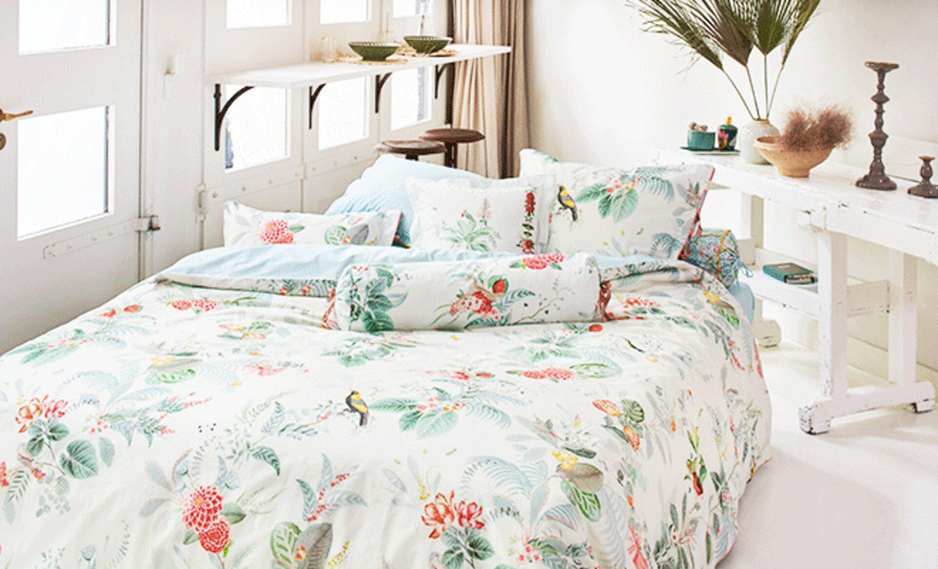 Polsterbett mit hell geblümter Bettwäsche als typisches Bett für das Schlafzimmer im Landhausstil. Dazu Möbel in weiß lasiertem Holz.