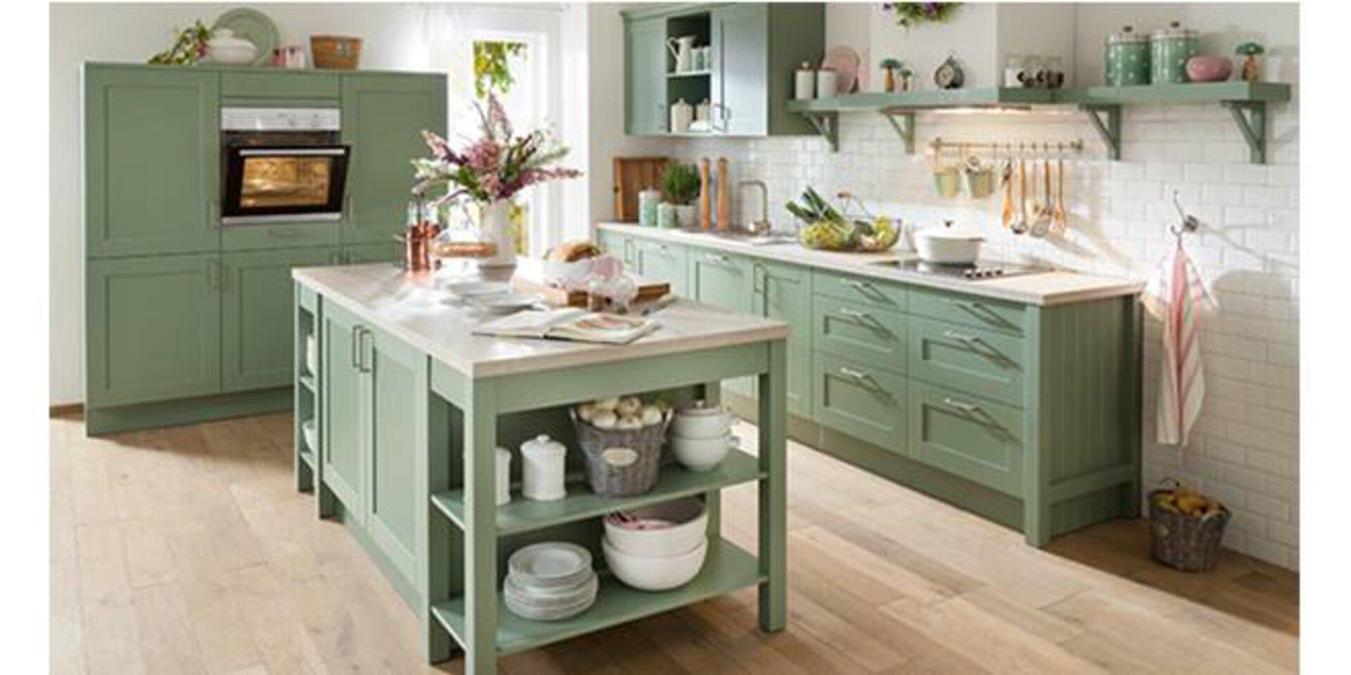 Planungsküche im Landhausstill mit grünen Holzmöbeln und rustikaler Kücheninsel.