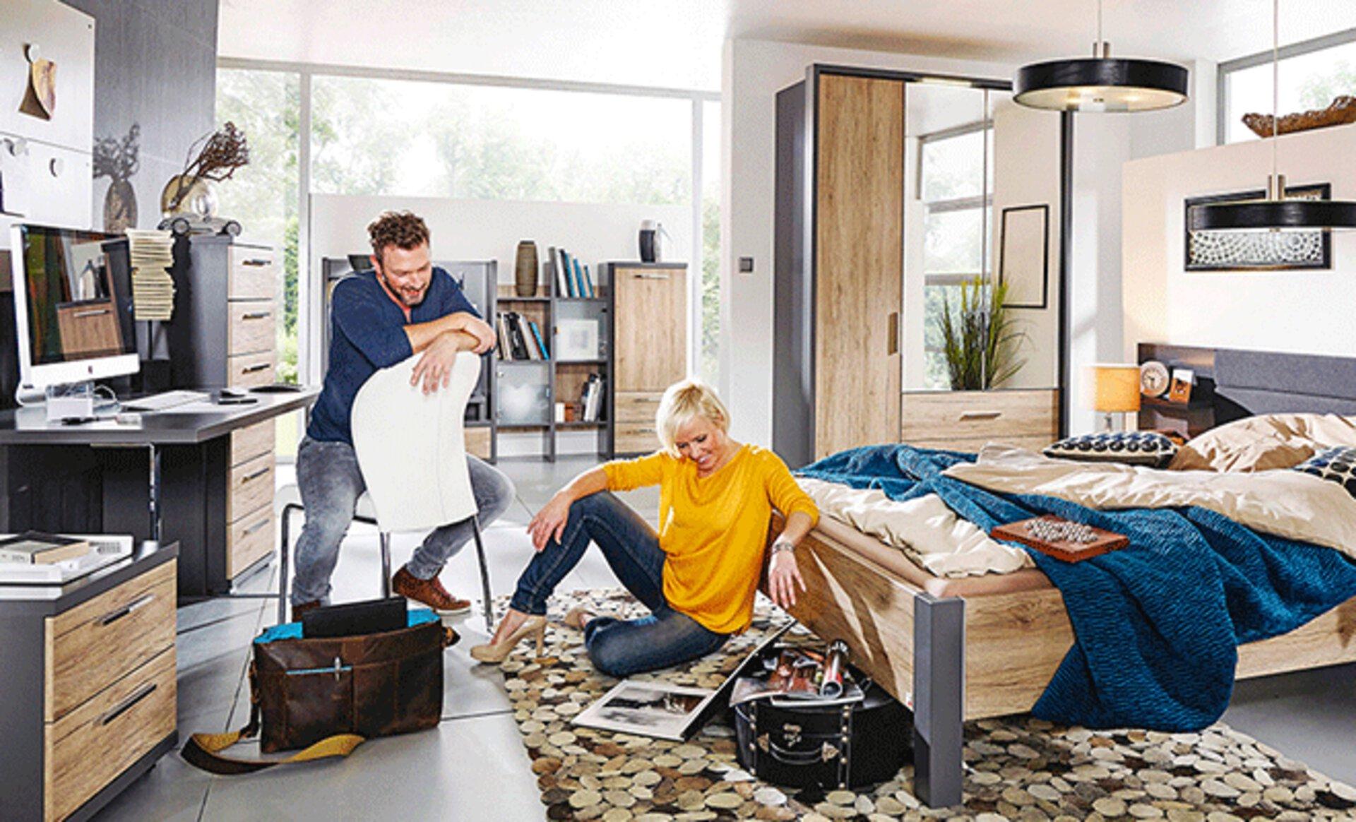WG-Zimmer Inspirationsbild zeigt gemütliches Zimmer mit Bett, Kleiderschrank, Schreibtisch und diversen Regalen. Möbel aus Holz und die Grundfarbe ist Hellgrau.