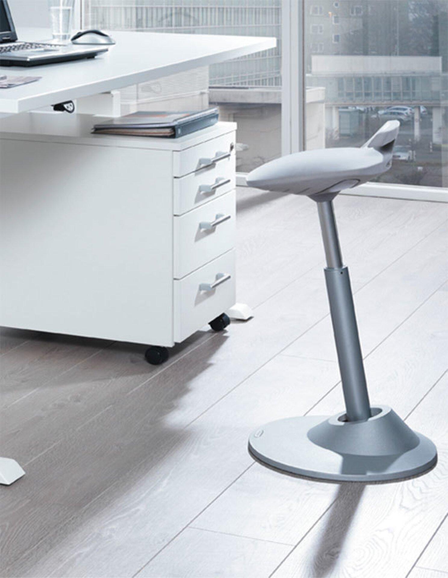 """Ergonomischer Sitzhocker mit grauem Bezug und höhenverstellbarem Stahlfuß auf rundem Sockel in einem hellen Arbeitszimmer dient als Titelbild für """"Der richtige Bürostuhl"""" auf der Startseite """"Inspiration""""."""