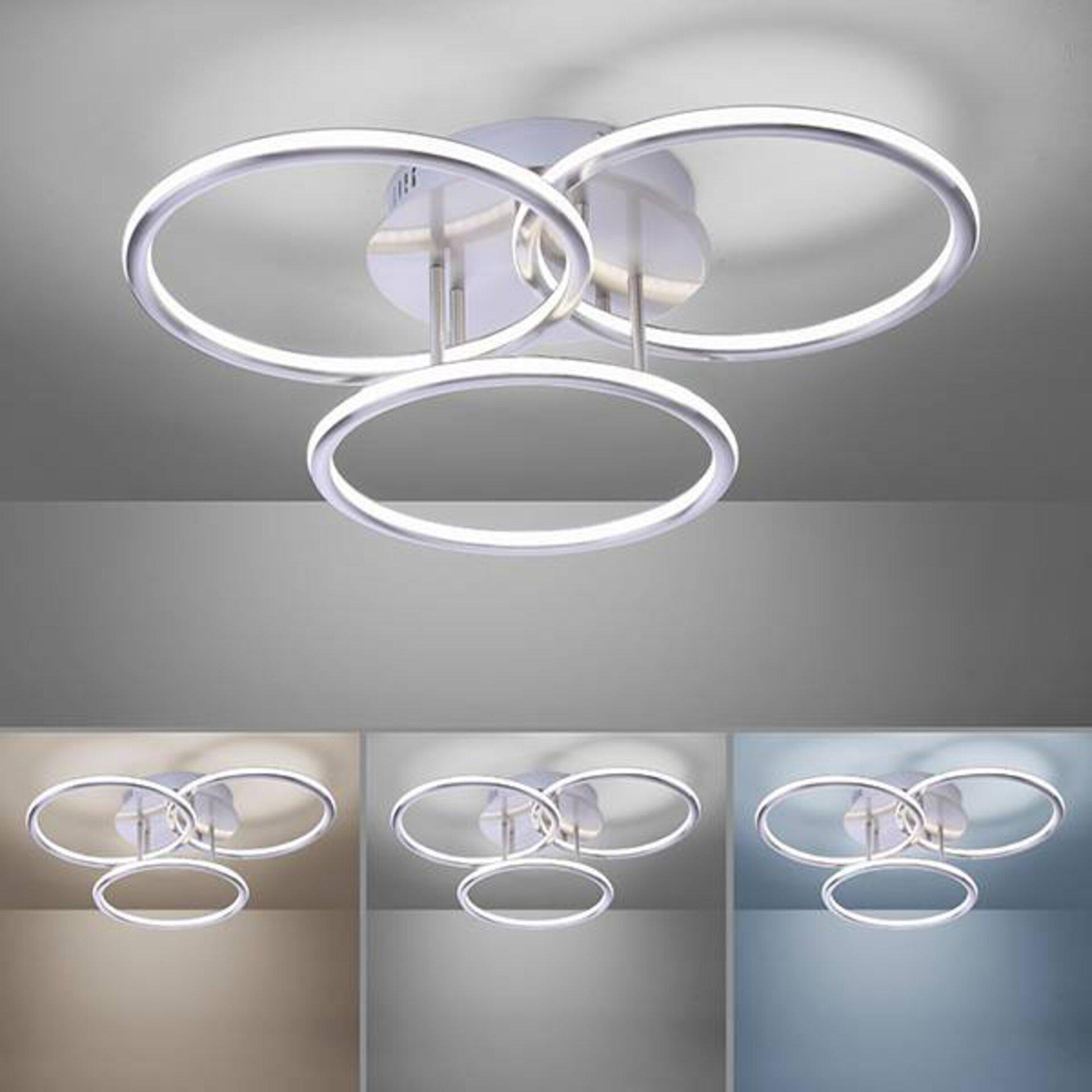 Hauptbild ist eine moderne Lampe aus drei Leuchtkreisen. Sie strahlt hell weiß. Darunter ist die gleiche Lampe kleiner in verschiedenen Leuchtfarben abgebildet.