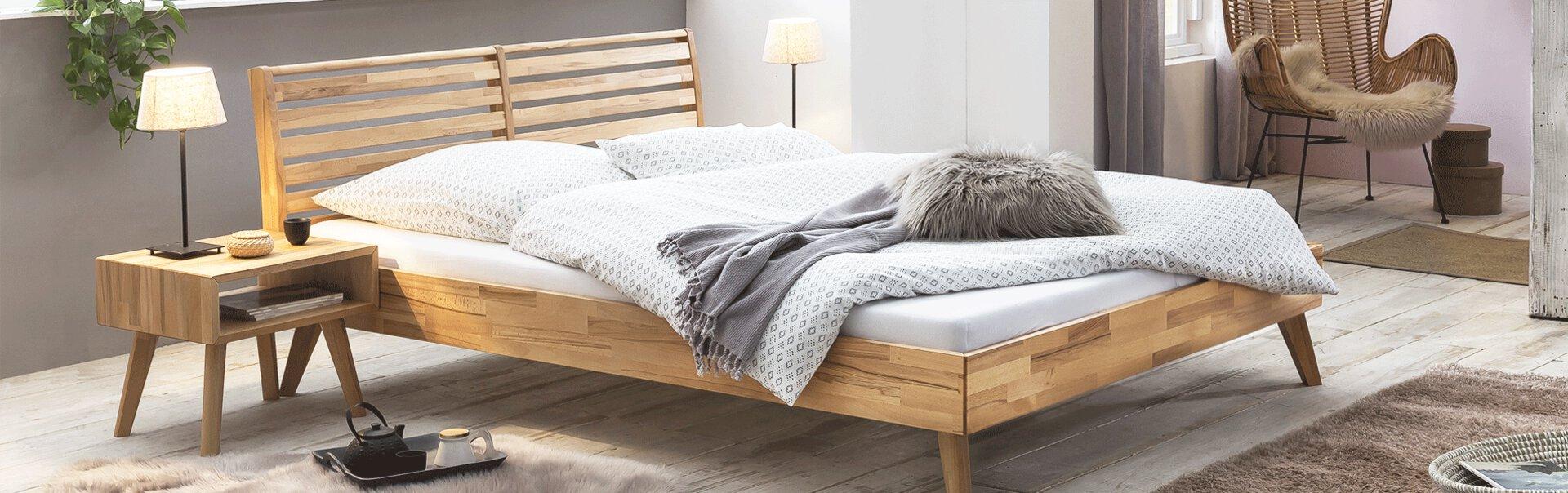 Bett und Nachttisch aus Massivholz. Dazu ein Fellteppich und weiße Bettwäsche.