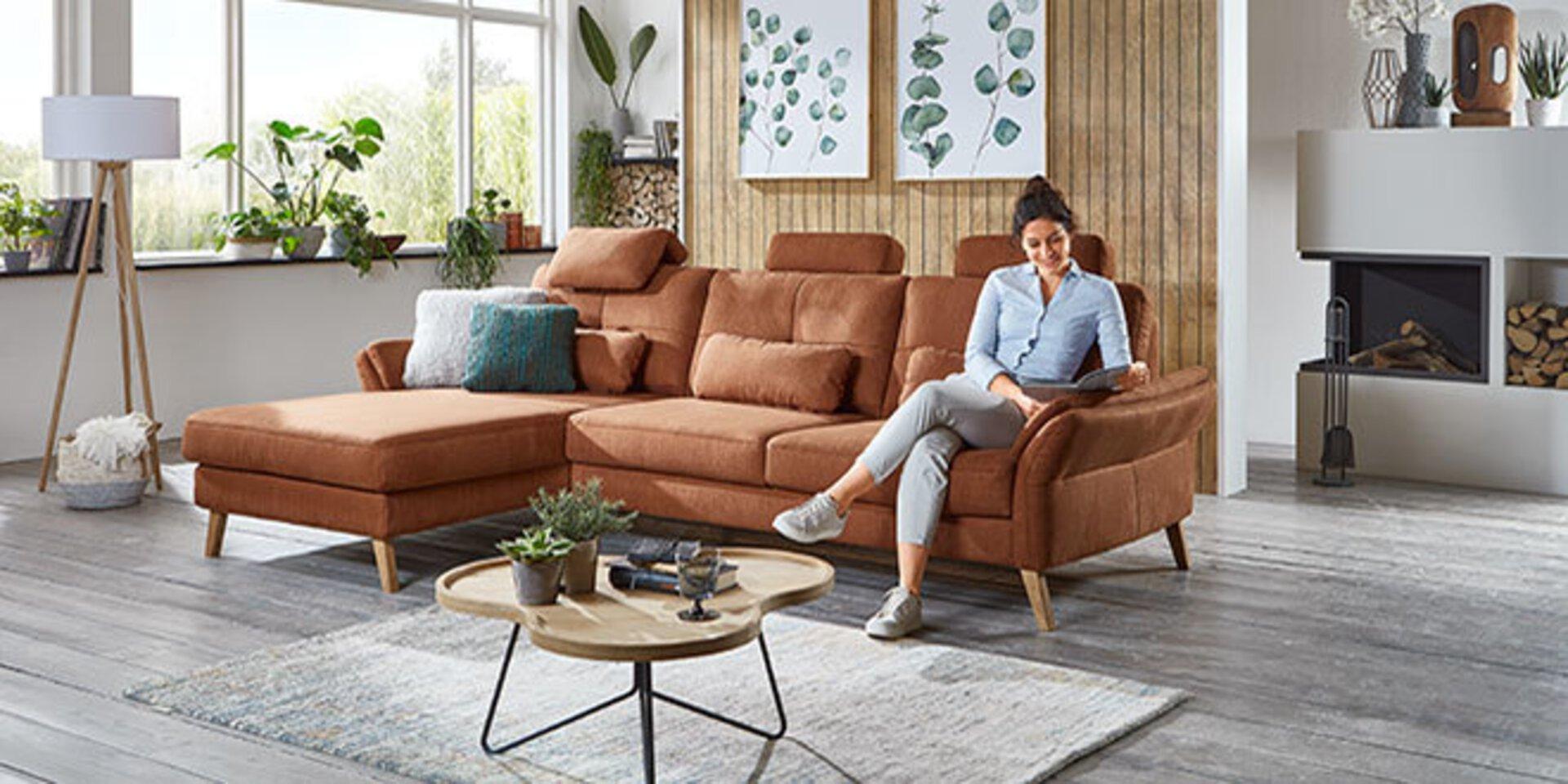 Weiteres Titelbild der Marke Valmondo zeigt ein Wohnzimmer mit gemütlichem Ecksofa in Fuchsbraun.