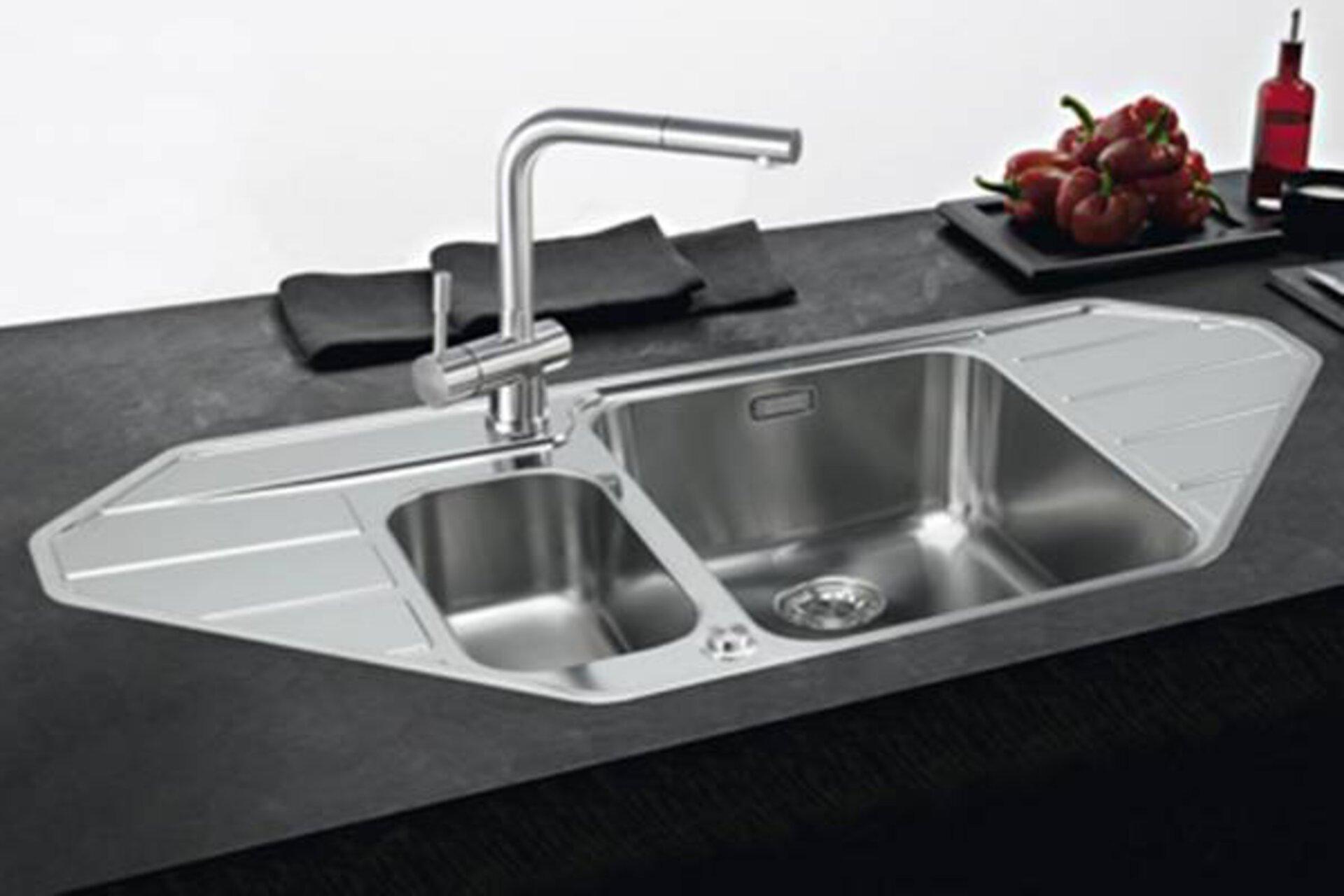 Edelstahlspüle mit großem quadratischem Becken und kleinem rechteckigen Spülbecken. Links und rechts der Becken ist eine Abtropffläche eingearbeitet. Das Bild dient als Kategoriebild für Küchenspülen