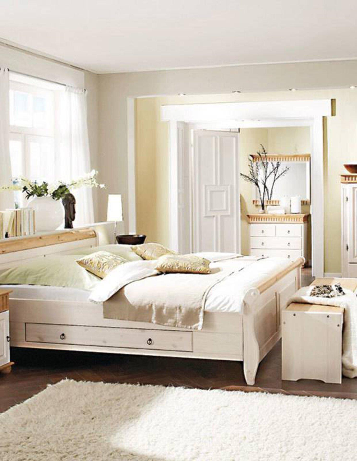 Schlafzimmer im Landhausstil zeigt großes Bett und breiten Kleiderschrank.- Die Möbel sind aus Holz, dabei sind einige Elemente naturbelassen, der Großteil jedoch weiß lasiert.