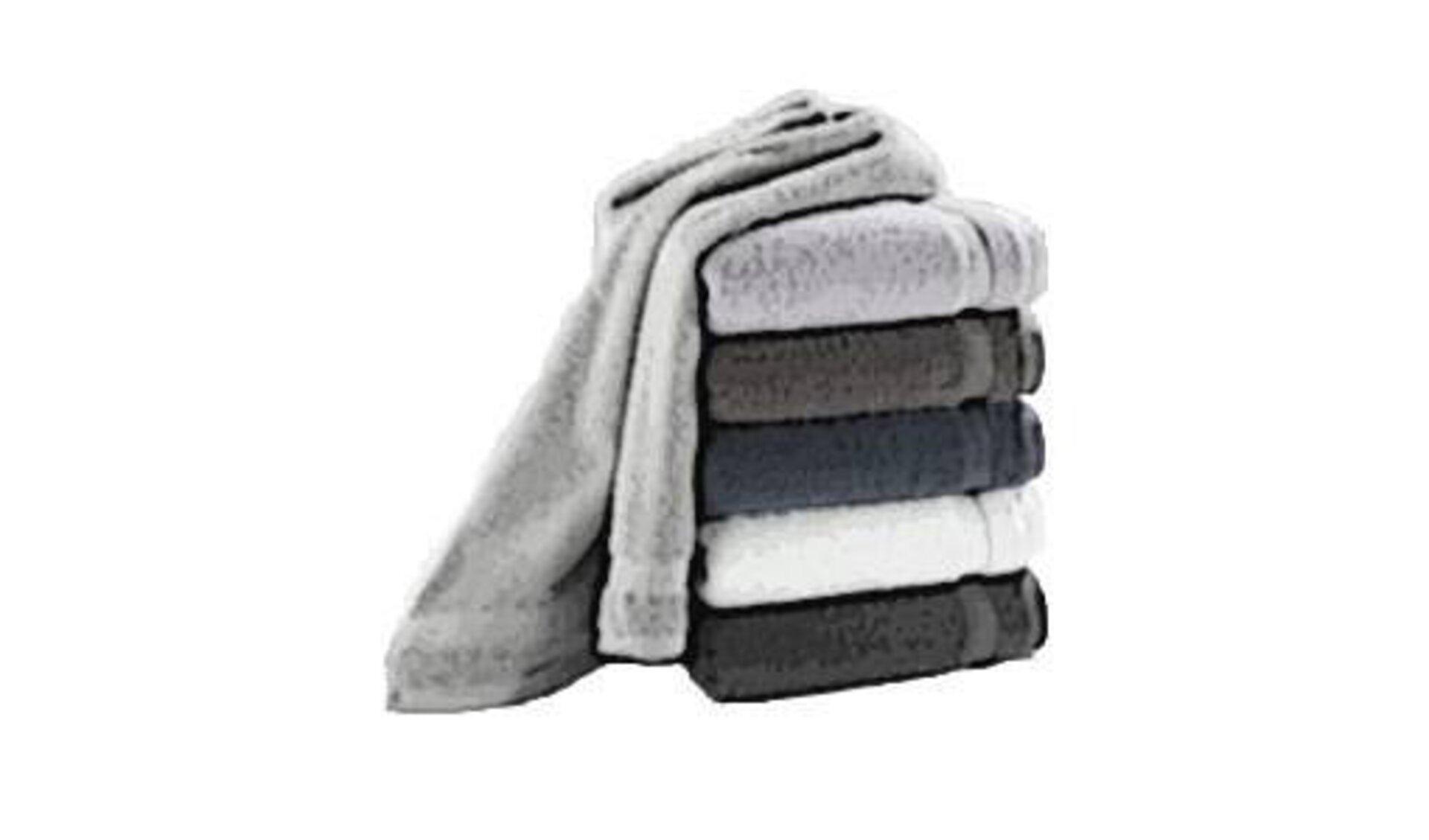 Badtextilien hier abgebildet als aufeinandergestapelte Handtücher in unterschiedlichen Grautönen. Das oberste Handtuch ist nicht zusammengelegt und hängt über die linke Seite am Stapel herab.