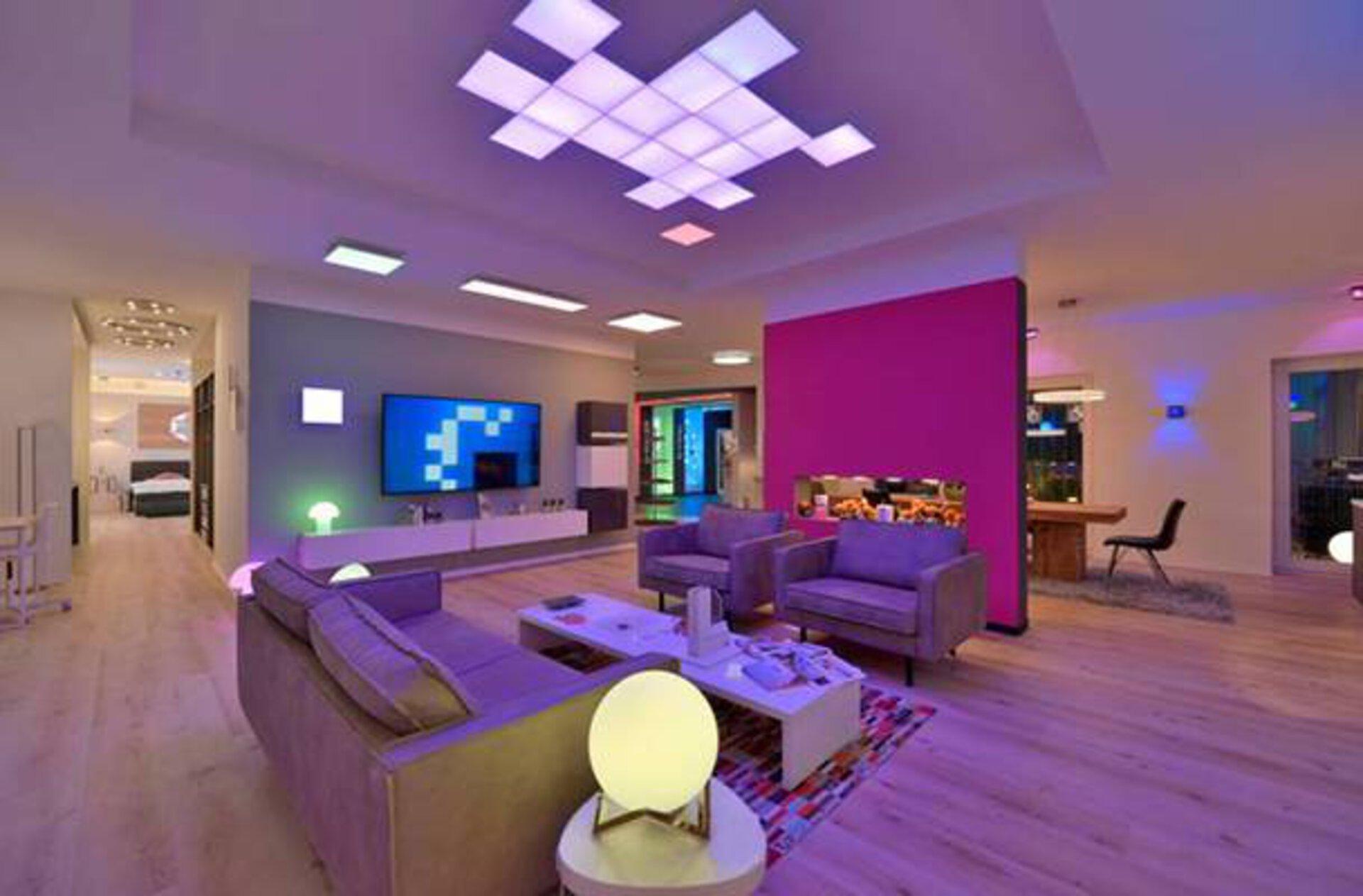 """Ein junges Wohnzimmer in buntes Licht getaucht als Milieubild für den Inspirationsbereich """"Smart Home""""."""