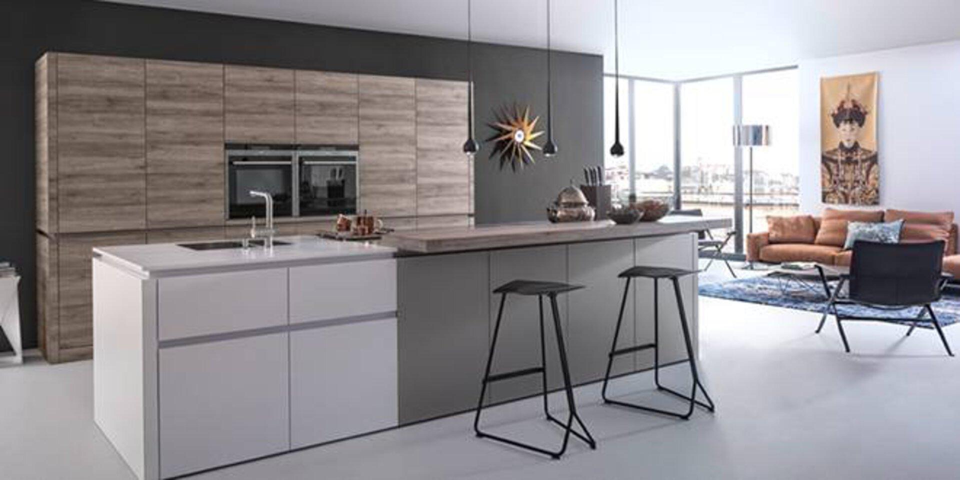 Titelbild der Markenseite zu LEICHT zeigt eine offene Wohnküche mit großer Kücheninsel in weiß und grau. Die Kücheninsel ist gleichzeitig Essenstheke und es stehen zwei moderne Barhocker davor.