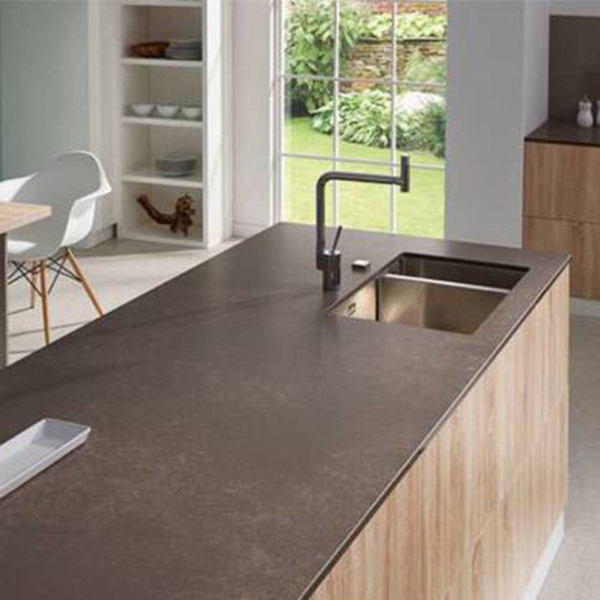 Millieubild zu Arbeitsplatten aus Kunststein. Zu sehen ist eine lange Kücheninsel mit eingelassener Spüle und bronze farbener Kunststeinarbeitsplatte.