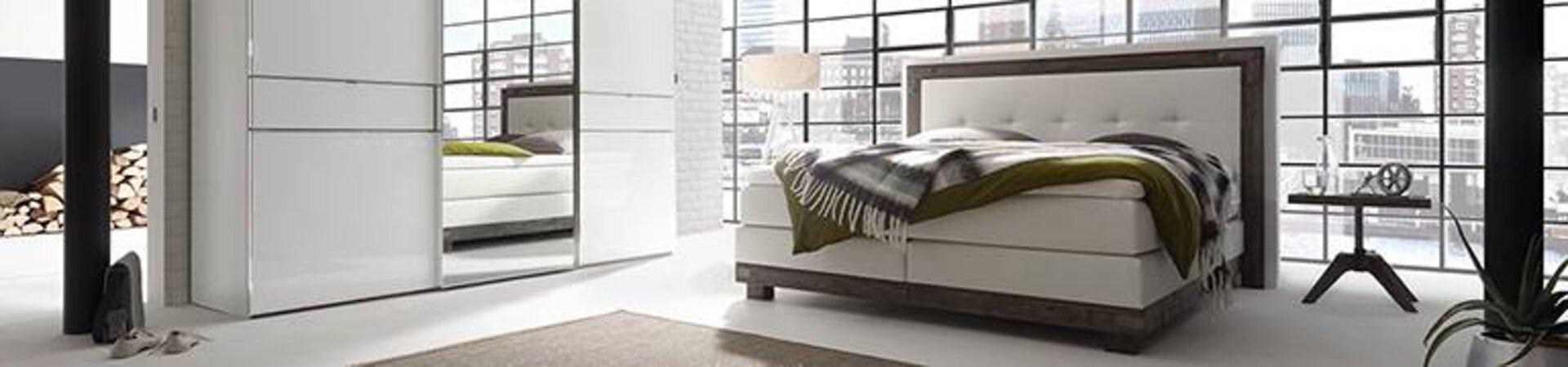 Ausschnitt eines Schlafzimmers, dass von einem großen Boxspringbett und einem weißen Schwebetürenschrank dominiert wird. Das Boxspringbett mit Doppelmatratze und lederbezogenem Kopfteil steht an einer großen Fensterfront in einem Loft.