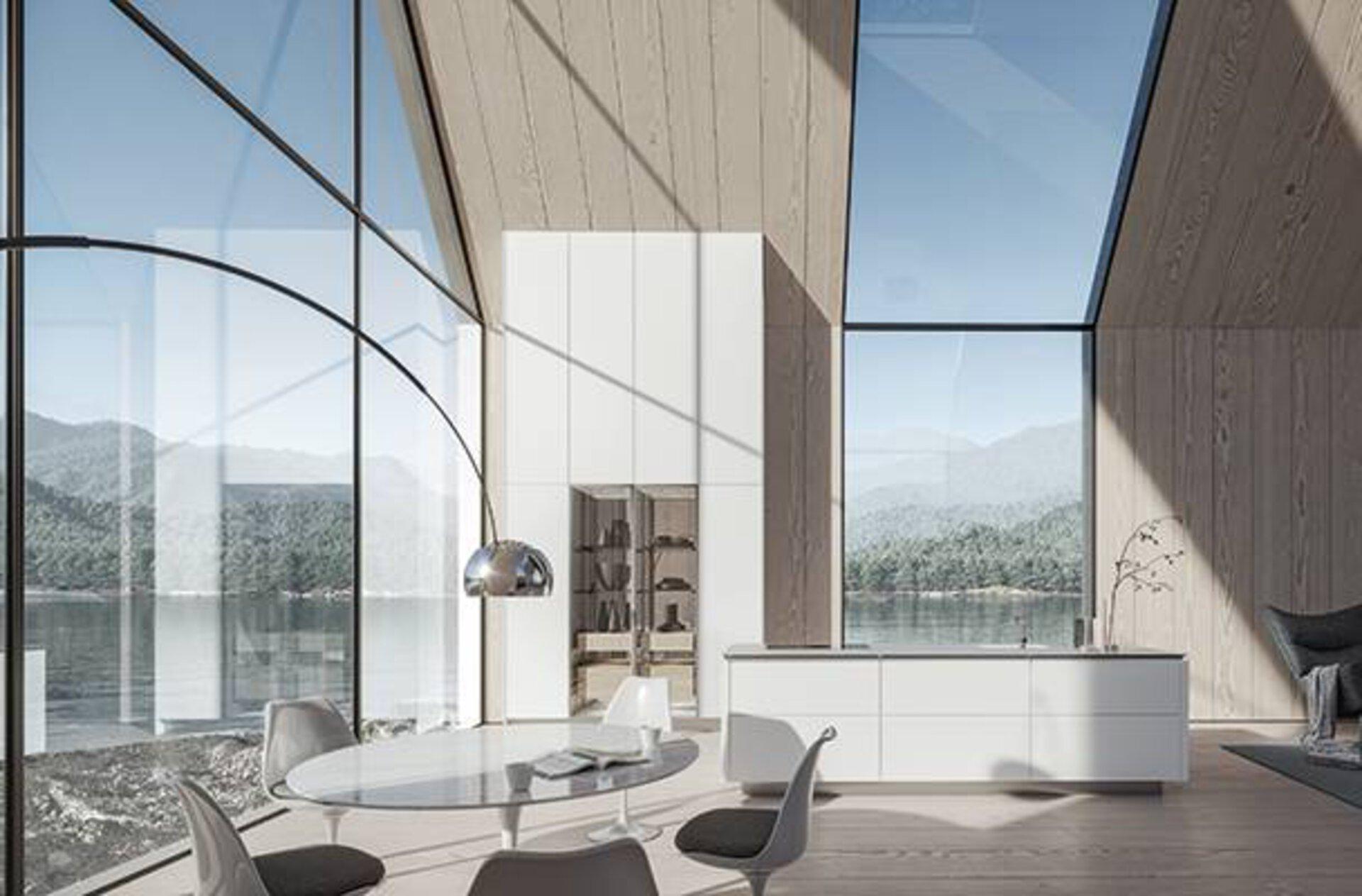Weiße Kücheninsel und hohe Küchenschränke neben einer  deckenhohen Glasfront ist das Aushängeschild der neuen SieMatic Küche und dient als Kategoriebild für den Premiumbereich First-Class-Küchen.