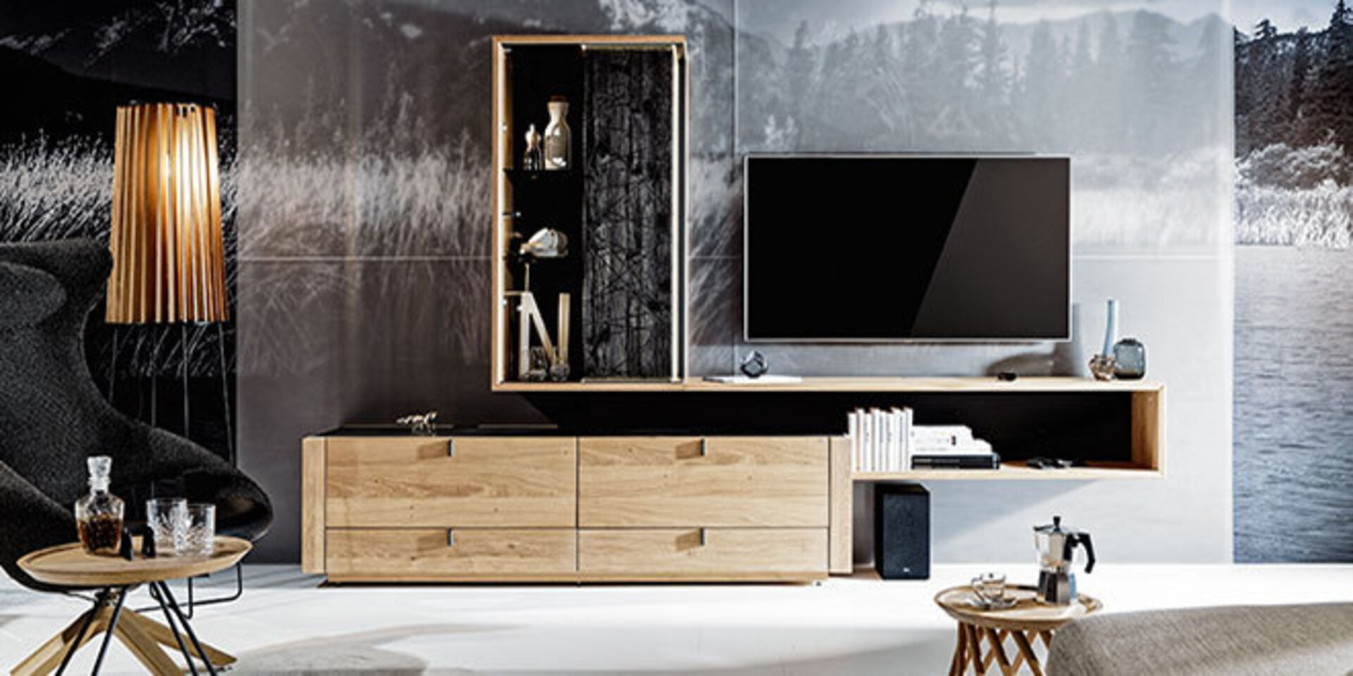 zweites Titelbild der Premiummarke Voglauer - Möbel voller Leben. Abgebildet ist  eine geradlinige Wohnwand aus Holz an einer schwarz-weißen Fototapete.
