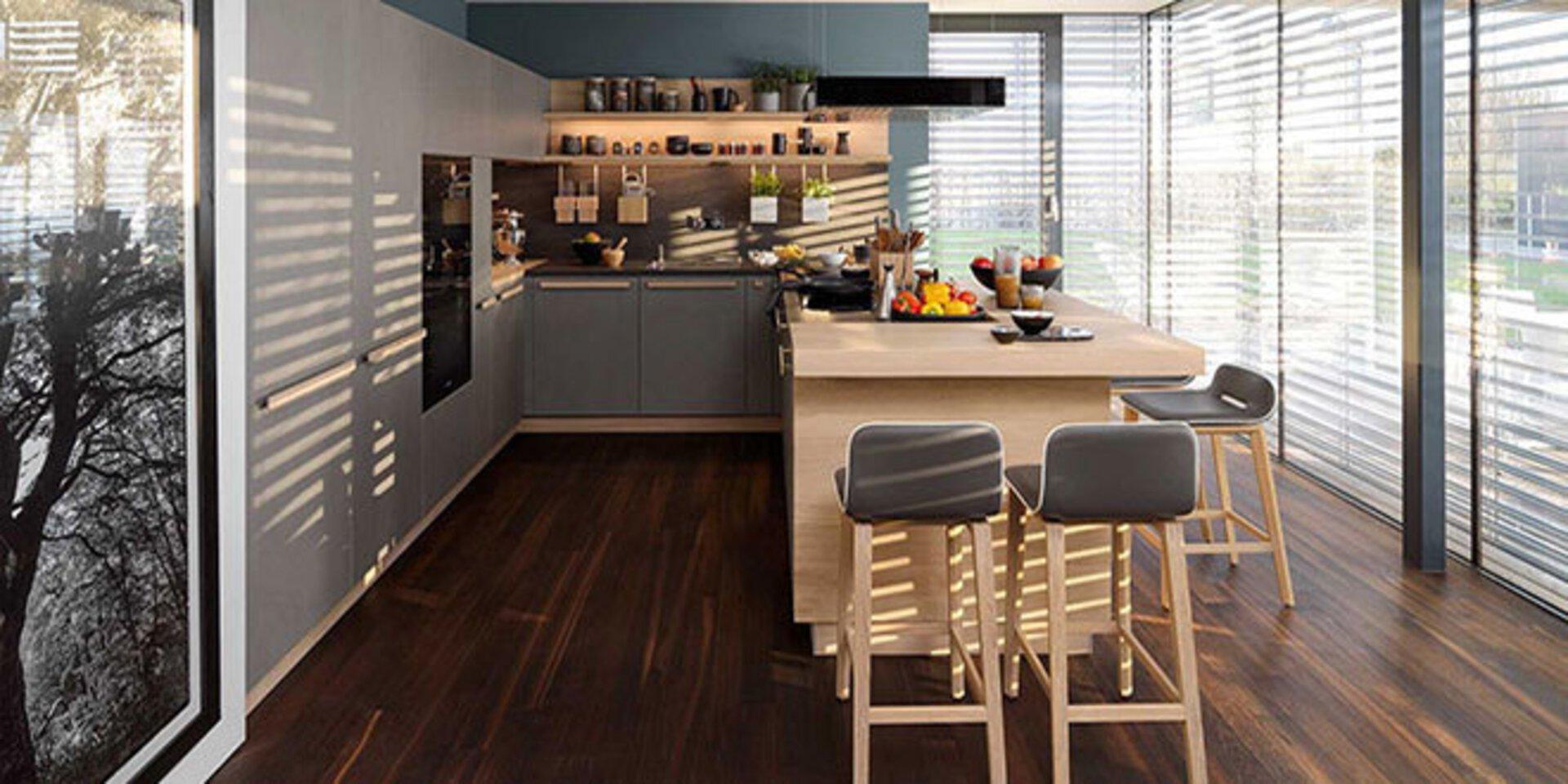 erstes Titelbild der Premiumpartner-Marke TEAM7 zeigt eine offene Küche in U-Form mit Theke und Barhockern.