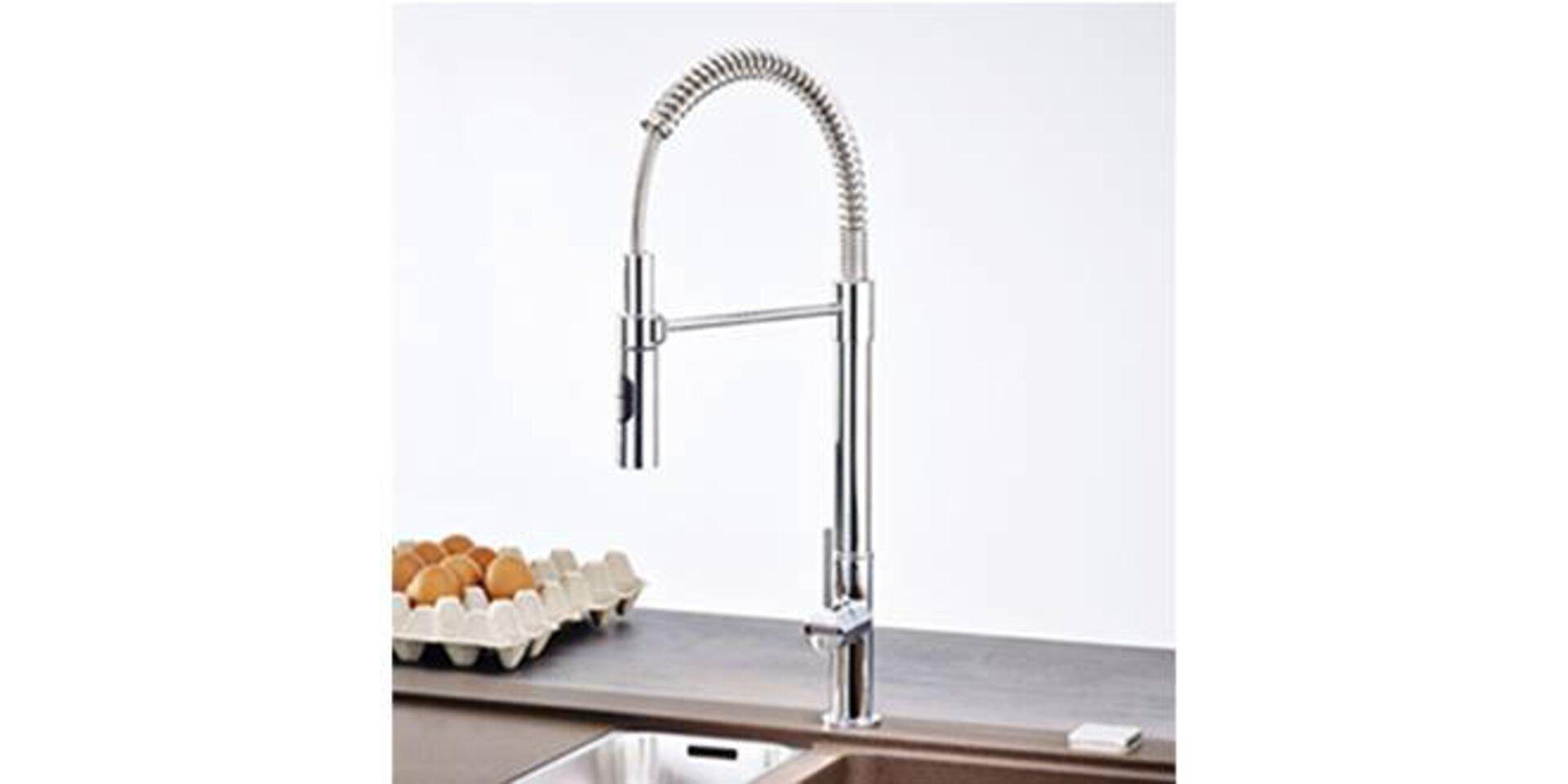 Hoher Wasserhahn aus Edelstahl mit Schlauchbrause als Armatur in der Küche.