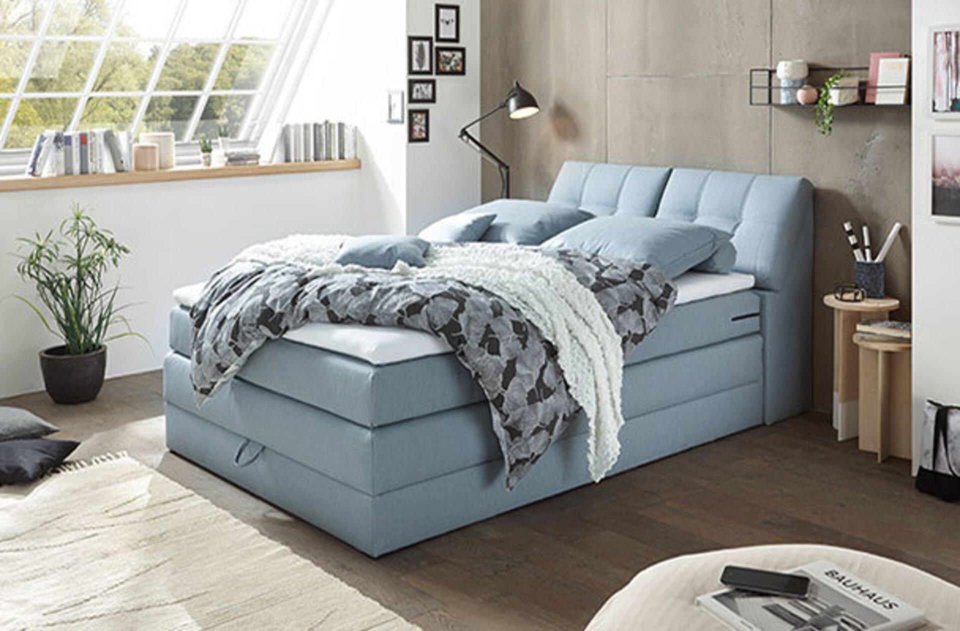 """Boxspringbett mit einer Liegefläche von 140x200 cm und hellblauem Polsterbezug. Das Bild dient als drittes Milieubild für den Inspirationsbereich  """"Boxspringbett""""."""